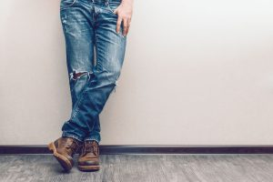 37468442 - young fashion man's legs in jeans and boots on wooden floor