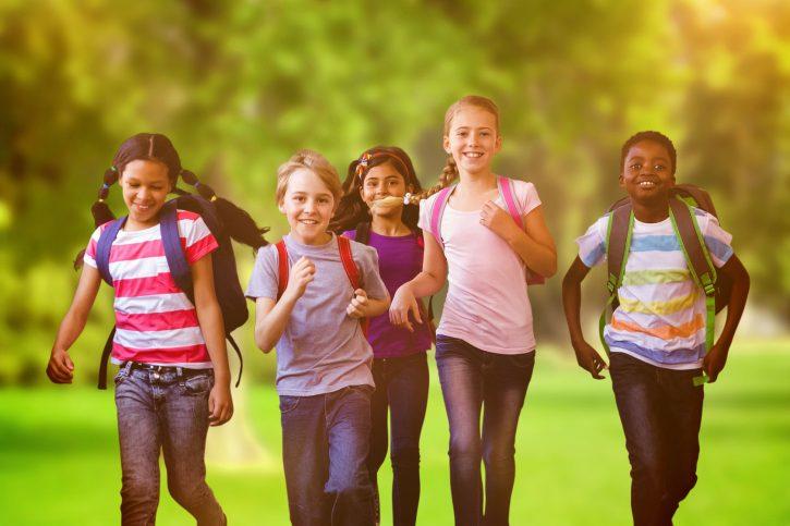 44598438 - school kids running in school corridor against trees and meadow