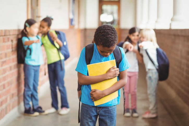 44851494 - sad pupil being bullied by classmates at corridor in school