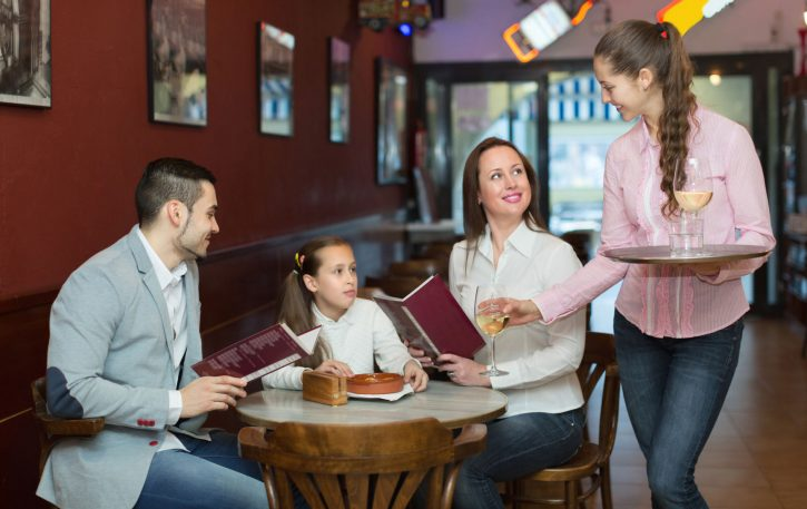 57952645 - smiling waitress and family with child at cafe. focus on waitress