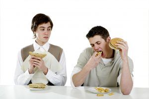 26231659 - man looking at his friend eating greedily