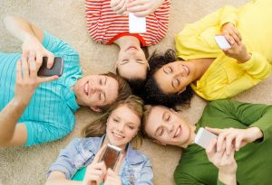 29244416 - education, technology and happiness concept - group of young smiling people lying down on floor in circle with smartphones