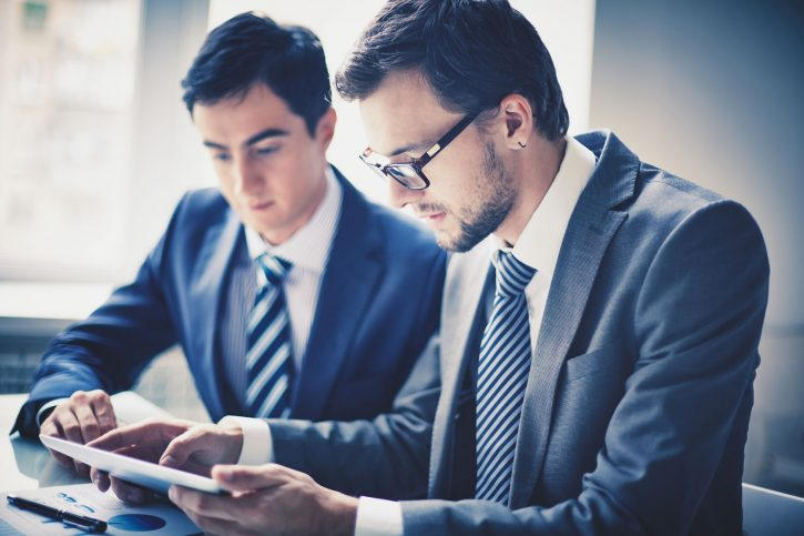23254841 - image of two young businessmen using touchpad