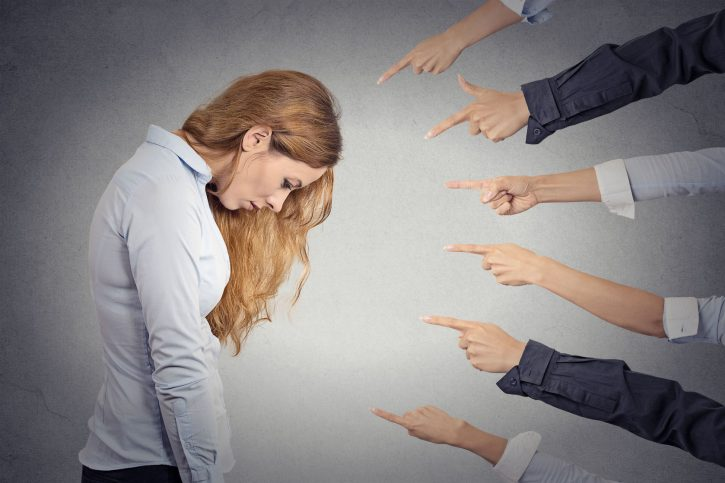 35166143 - concept of accusation of guilty businesswoman. side profile portrait sad upset woman looking down many fingers pointing at her isolated grey office background. human face expression emotion feeling