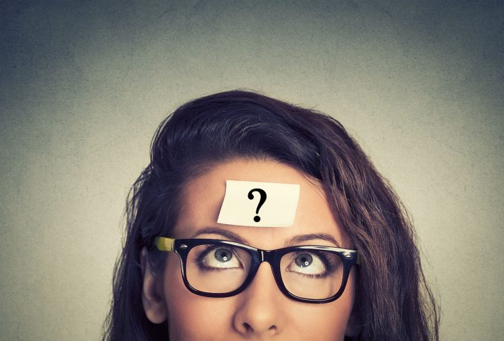 44333408 - thinking woman with question mark on gray wall background