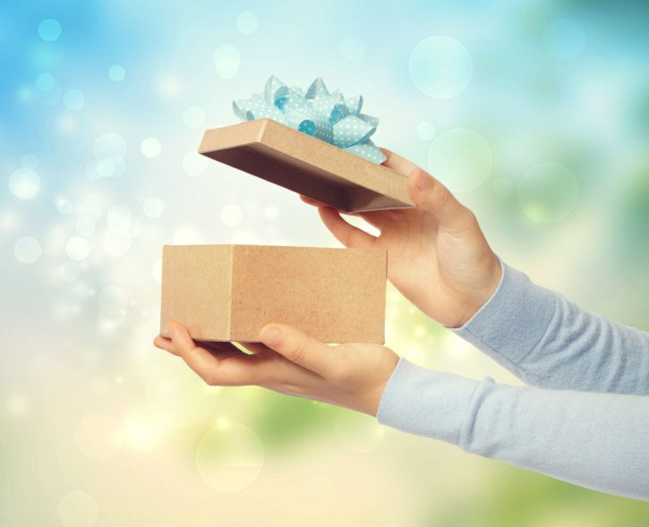 31371644 - woman opening and presenting gift box on bright background