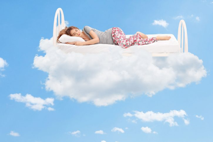 39577973 - relaxed young woman sleeping on a comfortable bed in the clouds