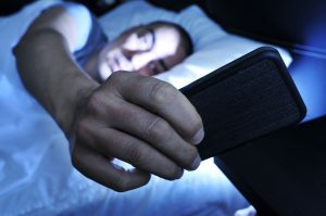 37559875 - closeup of a young man in bed looking at the smartphone at night